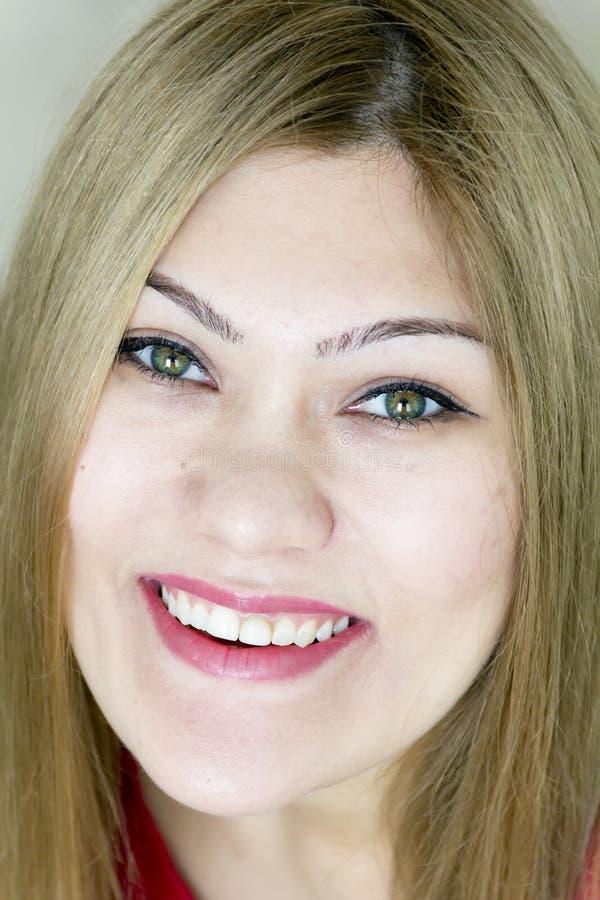 Uśmiechnięta młoda dziewczyna z prostym włosy i zielonymi oczami fotografia stock