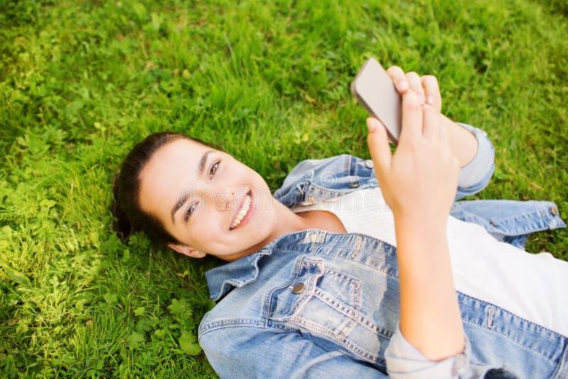 Uśmiechnięta młoda dziewczyna z smartphone lying on the beach na trawie zdjęcia stock