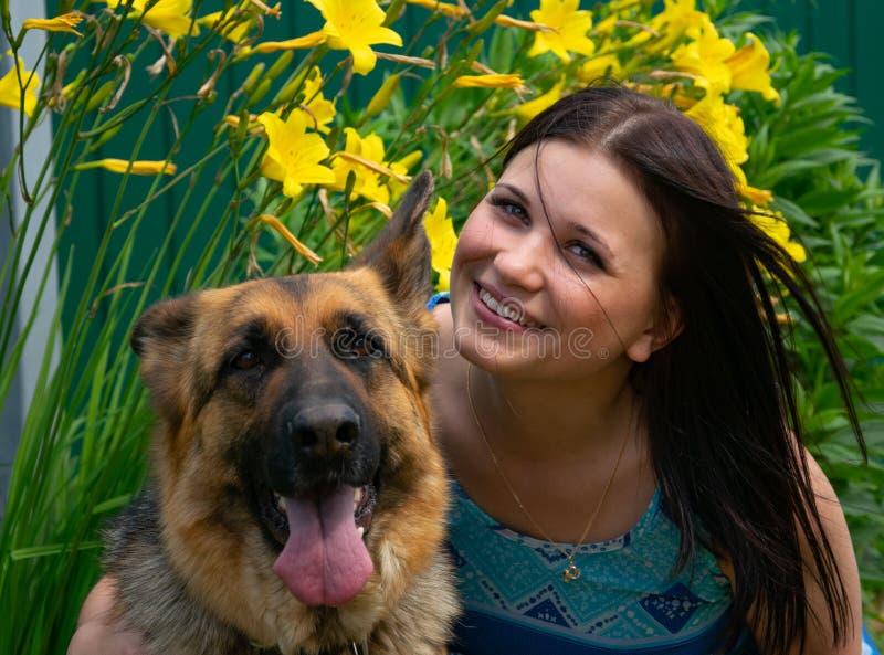 Uśmiechnięta młoda dziewczyna z wiernym przyjacielem na tle kwiaty obrazy royalty free