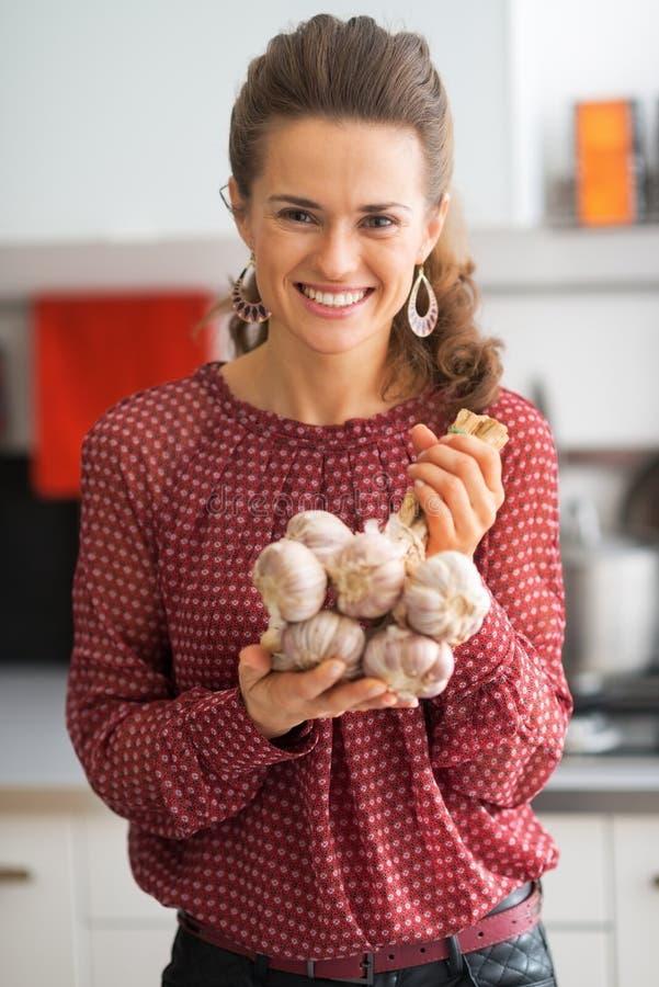 Uśmiechnięta młoda gospodyni domowa pokazuje wiązkę czosnek zdjęcie stock