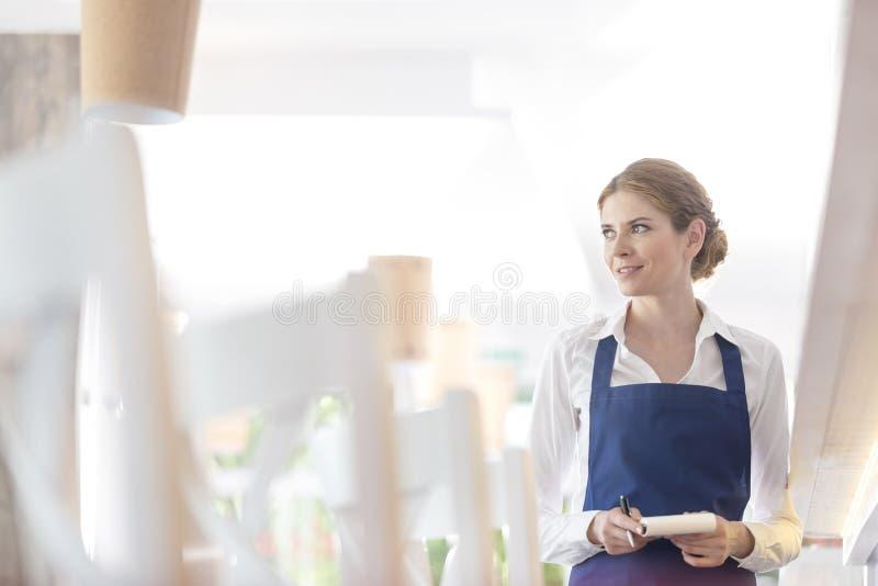 Uśmiechnięta młoda kelnerki pozycja z notepad podczas gdy patrzejący daleko od w restauracji zdjęcia royalty free