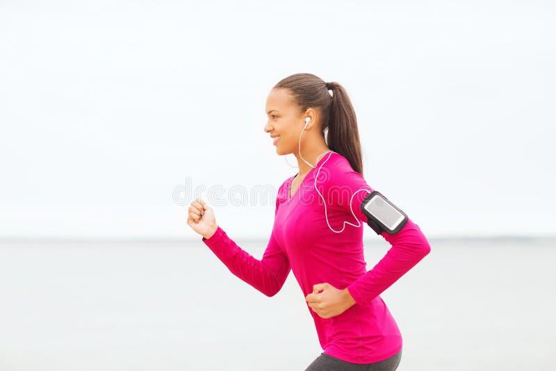 Uśmiechnięta młoda kobieta biega outdoors zdjęcie royalty free