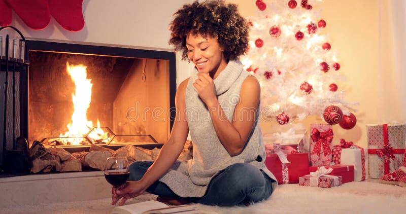Uśmiechnięta młoda kobieta cieszy się książkę przy bożymi narodzeniami obrazy royalty free