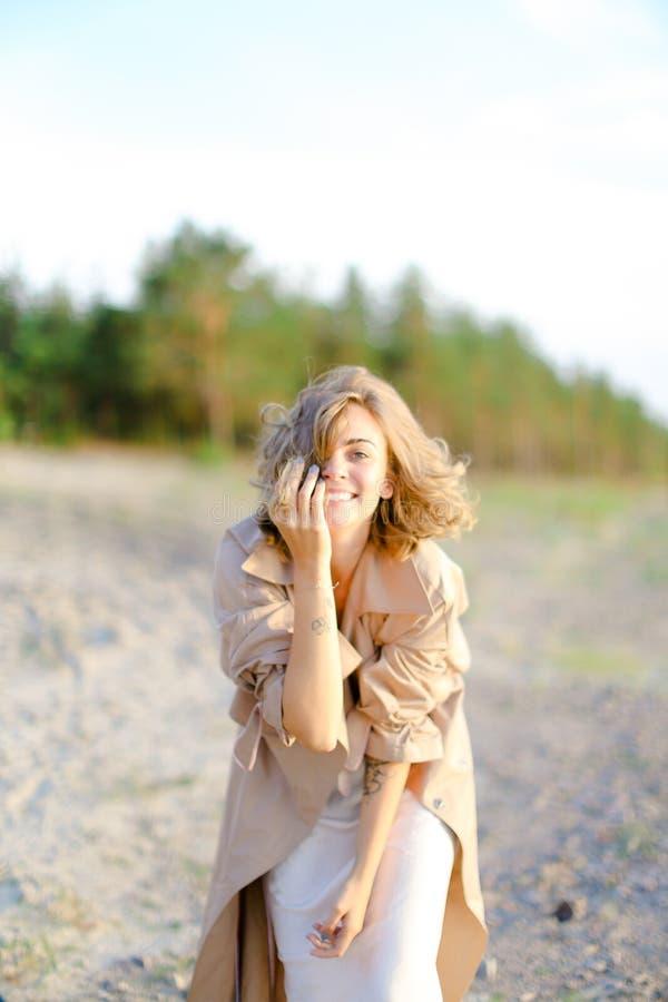 Uśmiechnięta młoda kobieta jest ubranym żakiet pozycję na piasku z drzewami w tle obraz stock