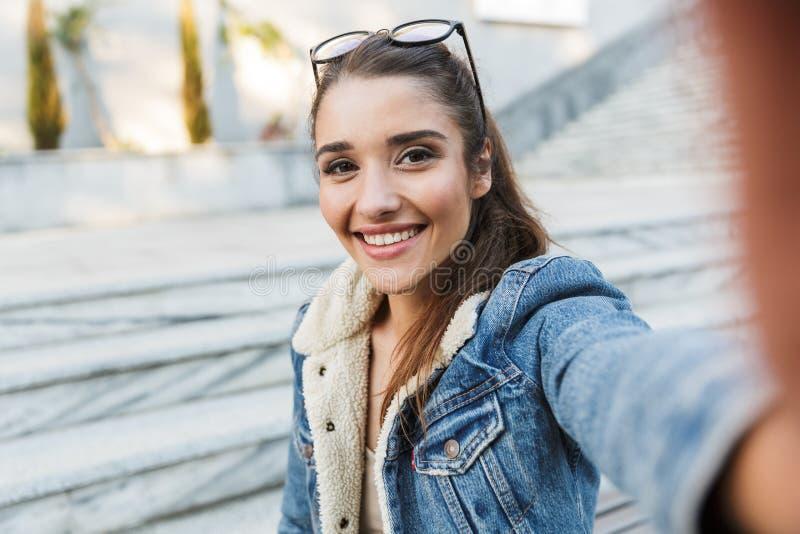 Uśmiechnięta młoda kobieta jest ubranym kurtki obsiadanie na ławce obraz stock