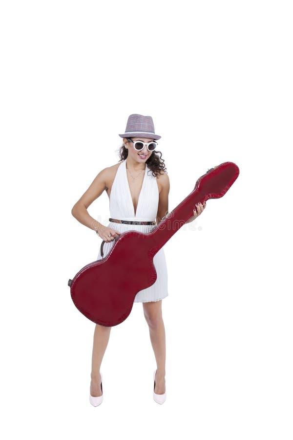 Uśmiechnięta młoda kobieta jest ubranym okulary przeciwsłonecznych pozuje z gitarą zdjęcie stock