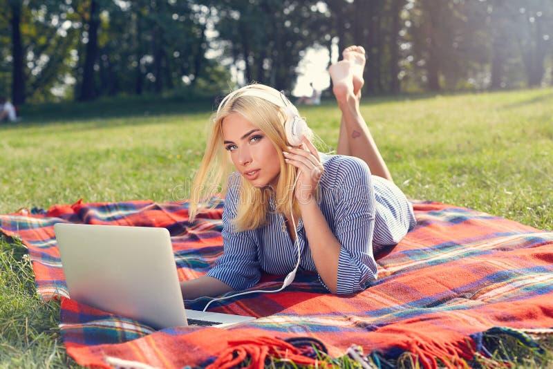 Uśmiechnięta młoda kobieta lub nastoletnia dziewczyna z laptopem i hełmofonami obrazy royalty free