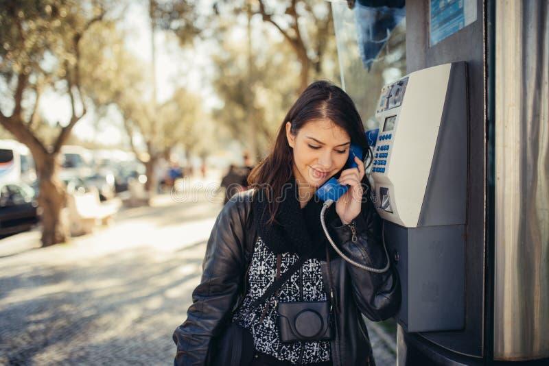 Uśmiechnięta młoda kobieta opowiada na jej smartphone na ulicie Komunikujący z przyjaciółmi, uwalnia wezwania i wiadomości dla mł zdjęcia royalty free