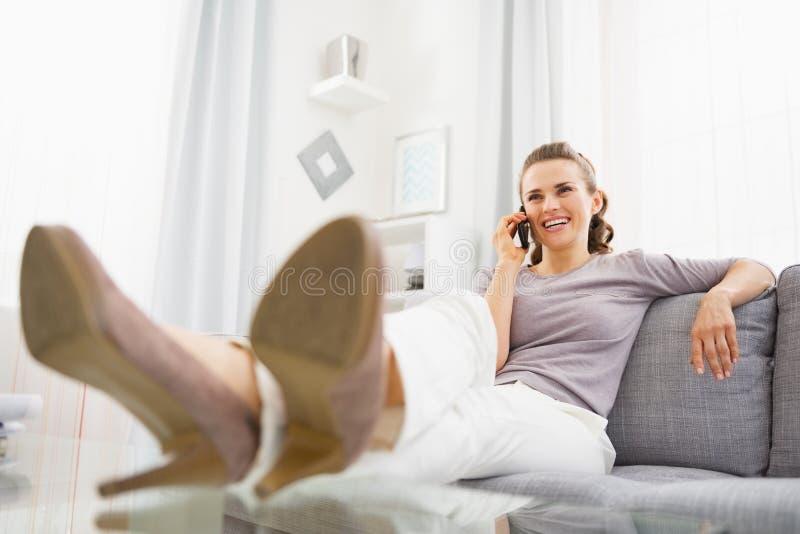 Uśmiechnięta młoda kobieta opowiada telefon komórkowego w żywym pokoju fotografia stock