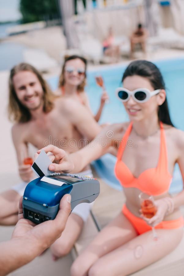 uśmiechnięta młoda kobieta płaci z kartą kredytową podczas gdy pijący szampana z przyjaciółmi fotografia royalty free