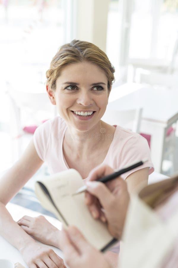 Uśmiechnięta młoda kobieta patrzeje kelnerki pisze rozkazie na notepad przy restauracją zdjęcie royalty free