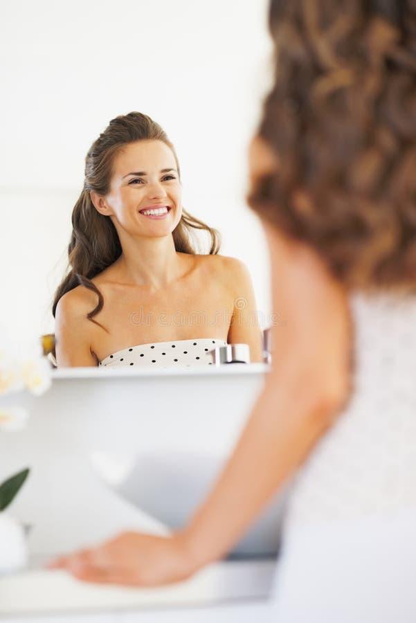 Uśmiechnięta młoda kobieta patrzeje w lustrze w łazience fotografia stock