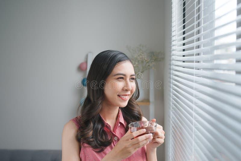 Uśmiechnięta młoda kobieta pije kawę lub herbata podczas gdy praca lub studiujemy a obrazy royalty free