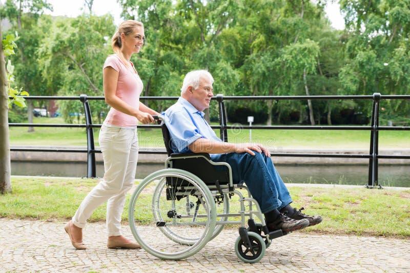 Uśmiechnięta młoda kobieta Pomaga Jej Niepełnosprawnego ojca Na wózku inwalidzkim zdjęcia stock