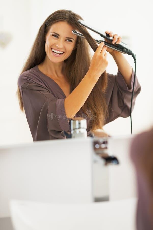 Uśmiechnięta młoda kobieta prostuje włosy z prostownicą zdjęcie stock