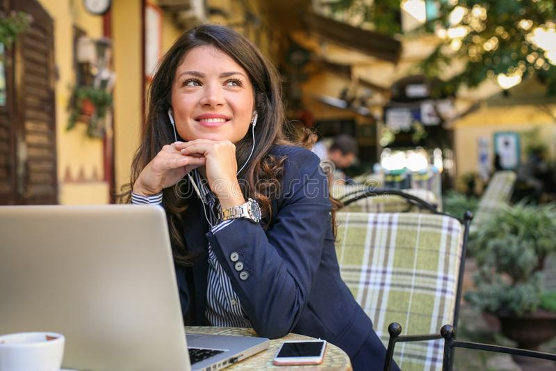 Uśmiechnięta młoda kobieta przy cukiernianą słuchającą muzyką, używać technologię zdjęcie stock