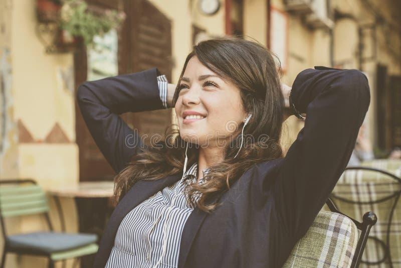 Uśmiechnięta młoda kobieta przy cukiernianą słuchającą muzyką z hełmofonami zdjęcia stock