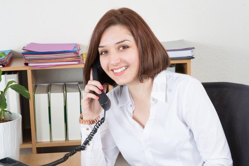 Uśmiechnięta młoda kobieta przy telefonem z klientem szczęśliwym przy ofice stołem i uśmiechem zdjęcia stock