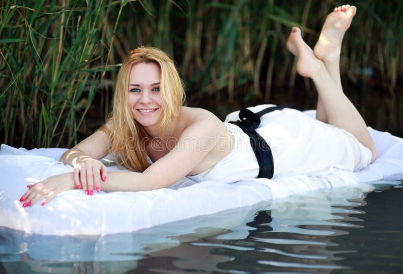 Uśmiechnięta młoda kobieta relaksuje w łóżku outdoors zdjęcie stock