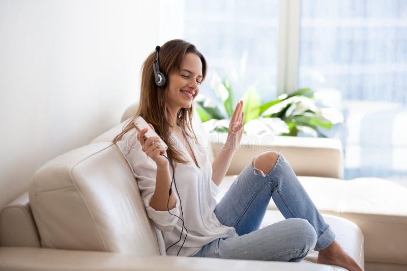 Uśmiechnięta młoda kobieta słucha muzyka na smartpho w hełmofonach fotografia royalty free