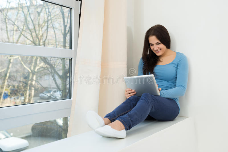 Uśmiechnięta młoda kobieta używa cyfrową pastylkę obrazy royalty free