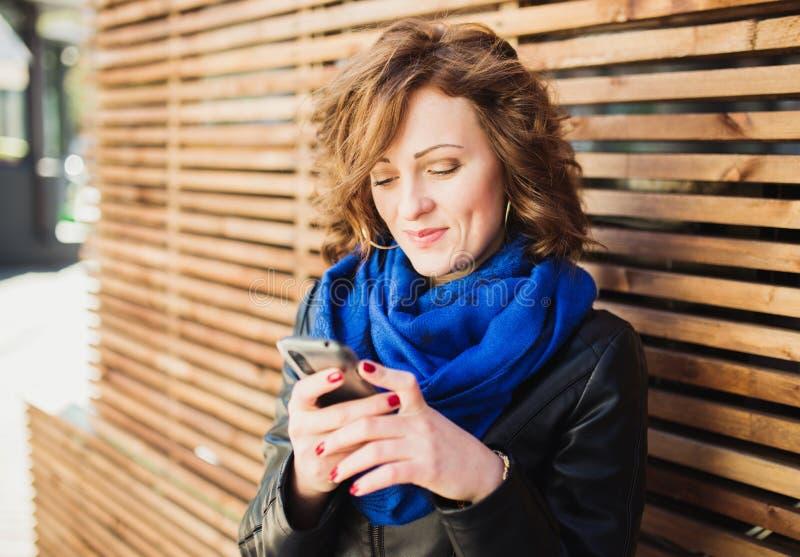 Uśmiechnięta młoda kobieta używa mobilnego mądrze telefon zdjęcie royalty free