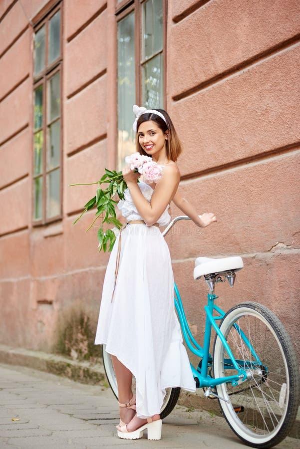 Uśmiechnięta młoda kobieta w bielu smokingowy pozować z peoniami blisko błękitnego roweru przed czerwonym dziejowym budynkiem zdjęcia stock