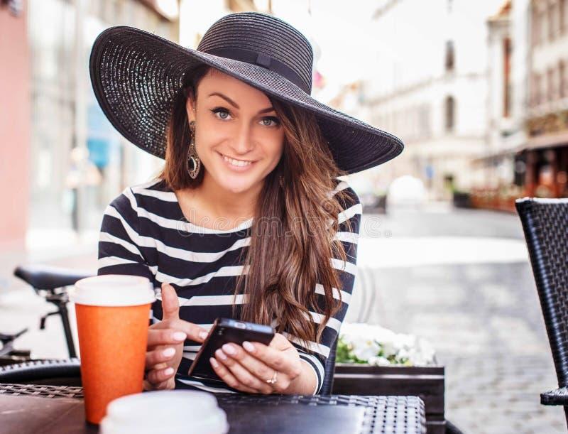 Uśmiechnięta młoda kobieta w czarnej koszula z białymi lampasami obraz stock