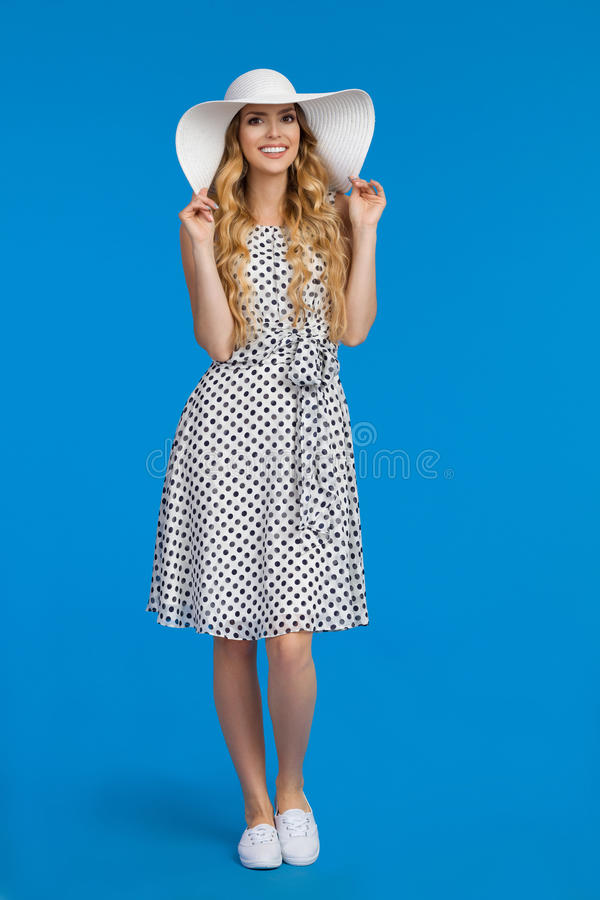 Uśmiechnięta młoda kobieta W kapeluszu, sukni I Sneakers Białych słońca, obrazy stock