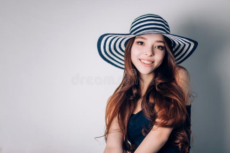 Uśmiechnięta młoda kobieta w słońce kapeluszu na plaży nad białym tłem wakacje letni, wakacje, podróż i ludzie, obraz stock