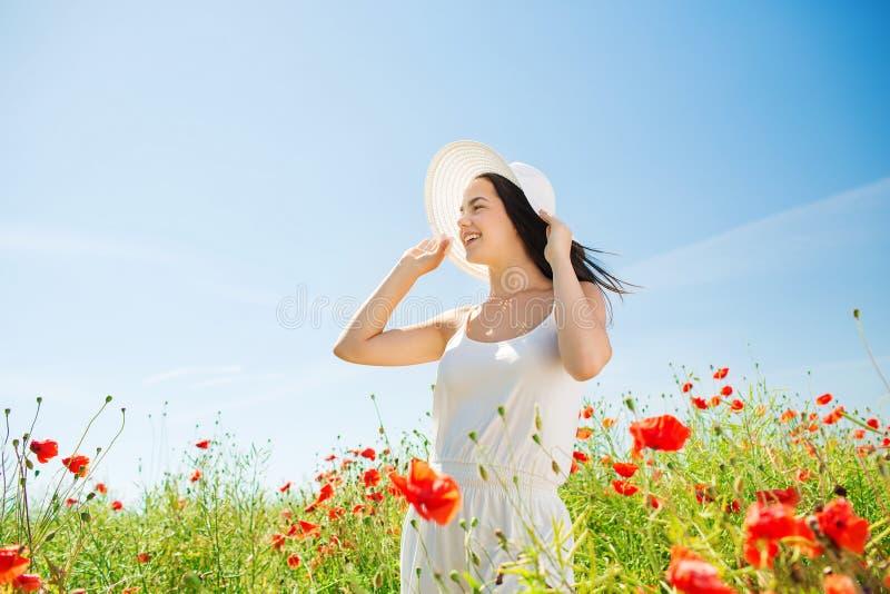 Uśmiechnięta młoda kobieta w słomianym kapeluszu na maczka polu zdjęcia royalty free