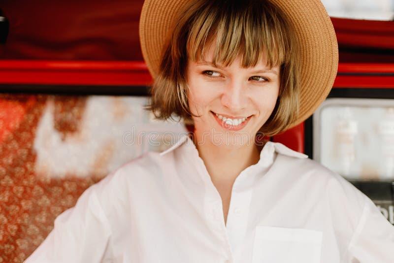Uśmiechnięta młoda kobieta w słomianym kapeluszu ubierał w białych koszulowych stojakach obok jaskrawej czerwieni i koloru żółteg zdjęcie stock