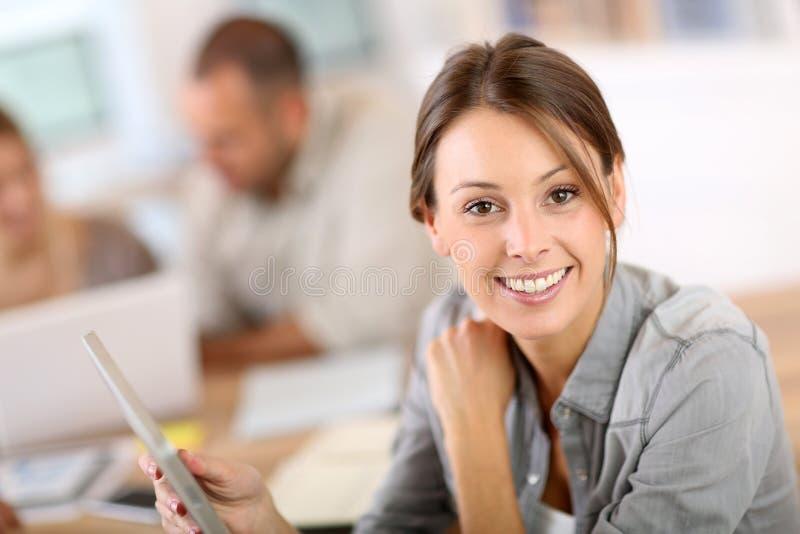 Uśmiechnięta młoda kobieta w stażowej klasie używa pastylkę obrazy stock