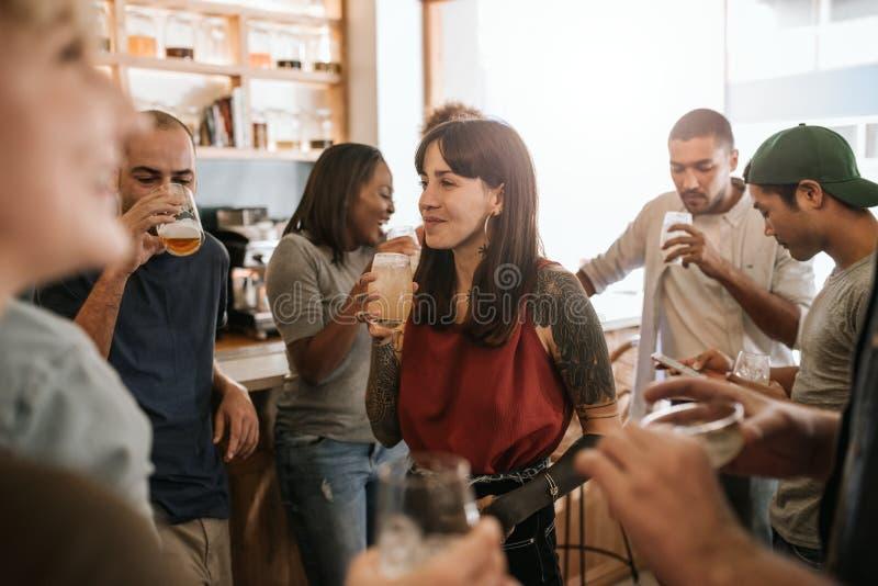 Uśmiechnięta młoda kobieta wisząca za przyjaciołach w barze z zdjęcie royalty free