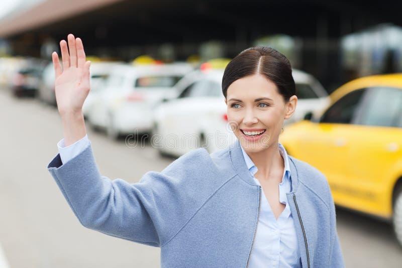 Uśmiechnięta młoda kobieta z falowaniem oddawał taxi zdjęcie stock