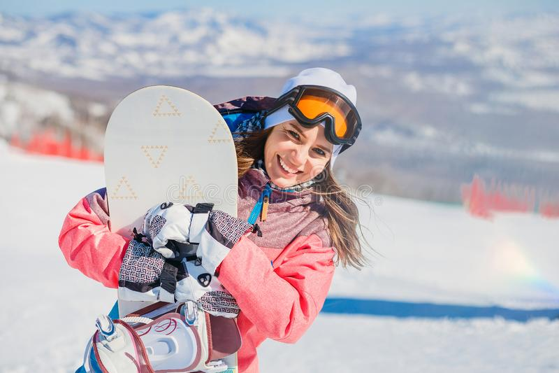 Uśmiechnięta młoda kobieta z jazda na snowboardzie na górze w zimie zdjęcia stock