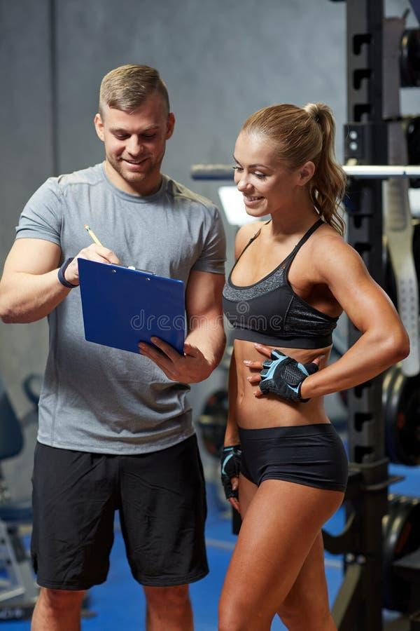 Uśmiechnięta młoda kobieta z osobistym trenerem w gym fotografia royalty free