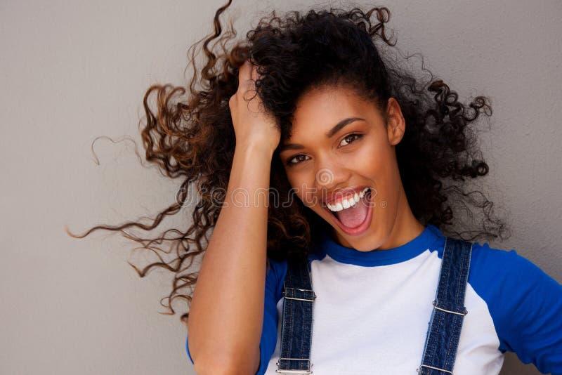 Uśmiechnięta młoda kobieta z ręką w włosy przeciw szaremu tłu zdjęcia royalty free