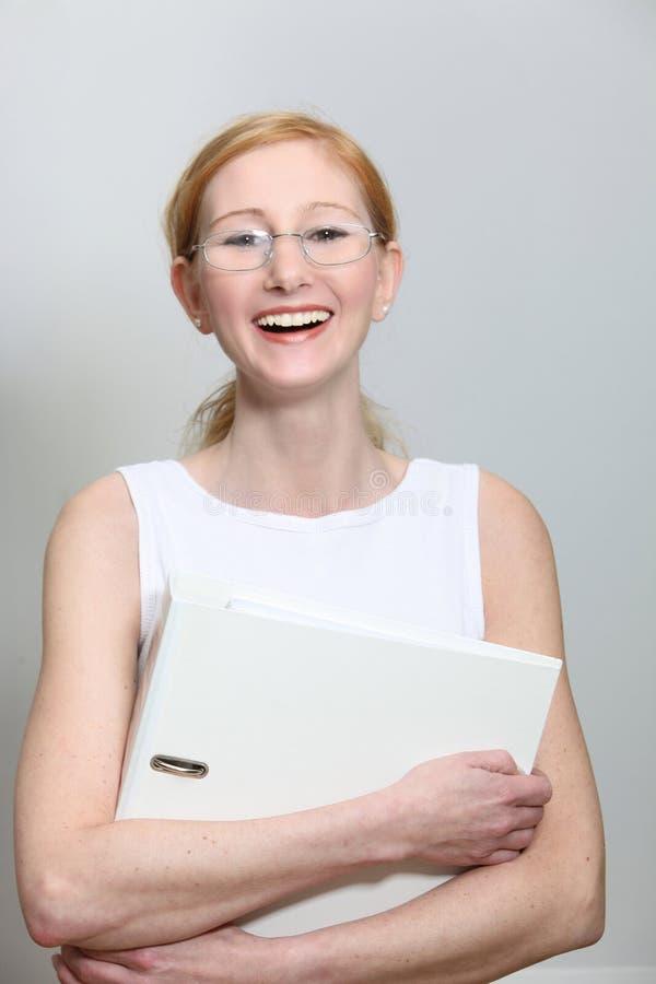 Uśmiechnięta młoda kobieta z szkłami i kartoteki falcówką obraz stock