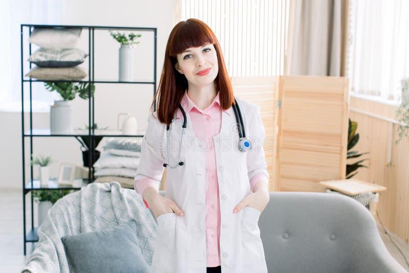 Uśmiechnięta młoda kobiety lekarka z stetoskopem na jej szyi, życzliwy pozytywny kobieta pediatry wizyty klient daje do domu zdjęcia stock