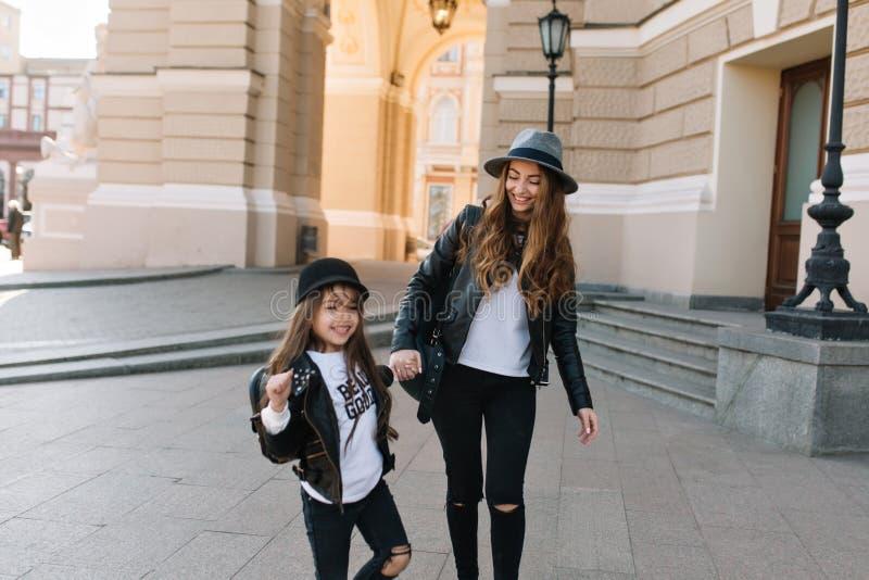 Uśmiechnięta młoda mama i córka wpólnie chodzi wokoło miasteczka w ten sam białych koszula wydaje czas Rozochocony kędzierzawy obraz stock