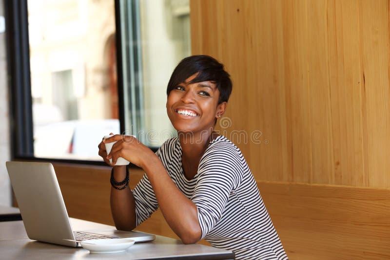 Uśmiechnięta młoda murzynka z kawą i laptopem przy kawiarnią obrazy royalty free