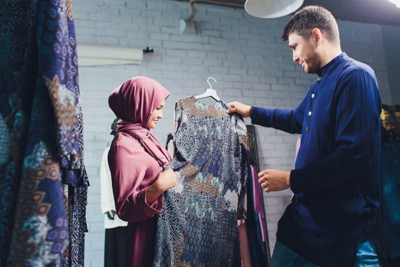 Uśmiechnięta młoda muzułmańska para kupuje i patrzy na dywany w sklepie z wyrobami włókienniczymi obraz stock