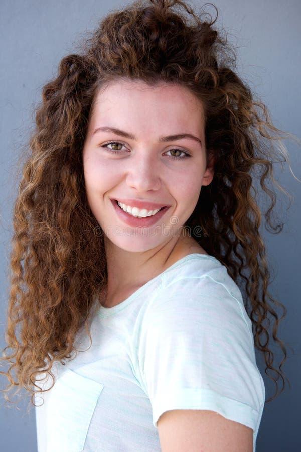 Uśmiechnięta młoda nastoletnia dziewczyna przeciw szarości ścianie obrazy royalty free