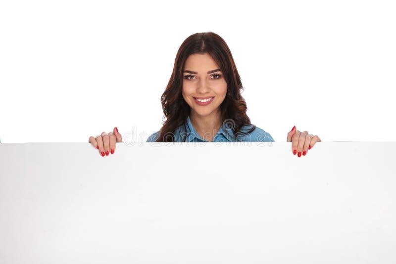 Uśmiechnięta młoda przypadkowa kobieta trzyma wielkiego billboard zdjęcia royalty free