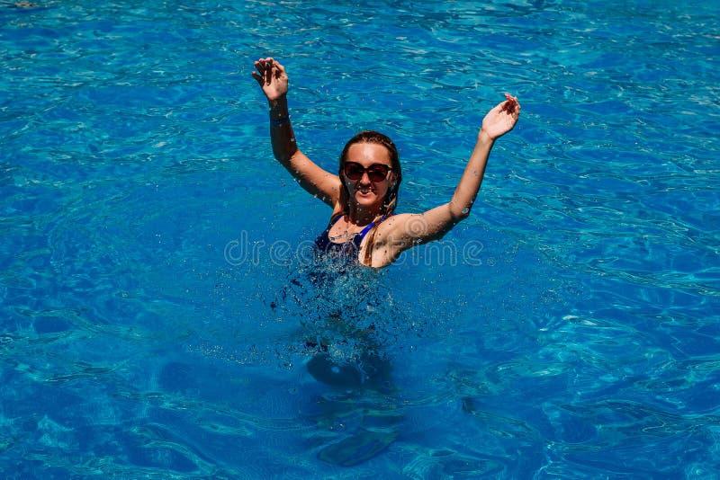 Uśmiechnięta młoda szczęśliwa kobieta w błękitne wody basenie zdjęcie royalty free