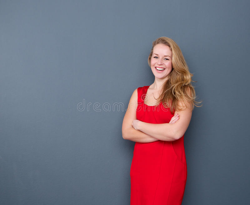 Uśmiechnięta młodej kobiety pozycja na szarym tle fotografia stock