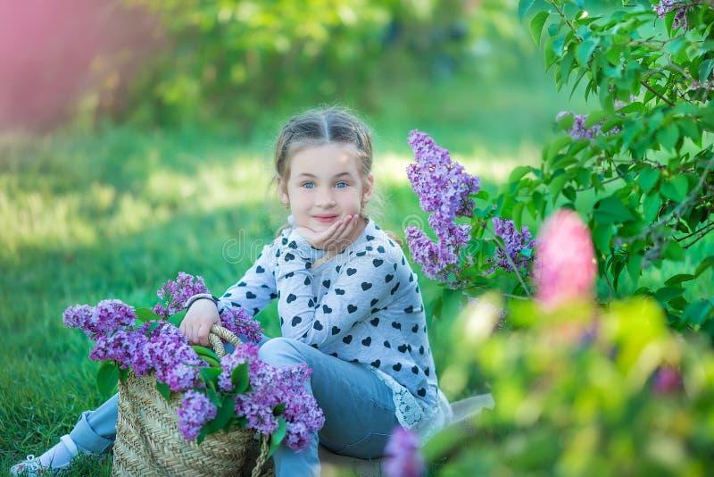 Uśmiechnięta mała śliczna blondynki dziecka dziewczyna 4-9 rok z bukietem bez w rękach w cajgach i koszula zdjęcie stock