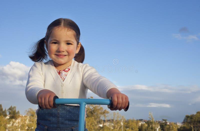 Uśmiechnięta mała dziewczynka bawić się z hulajnogą zdjęcia royalty free