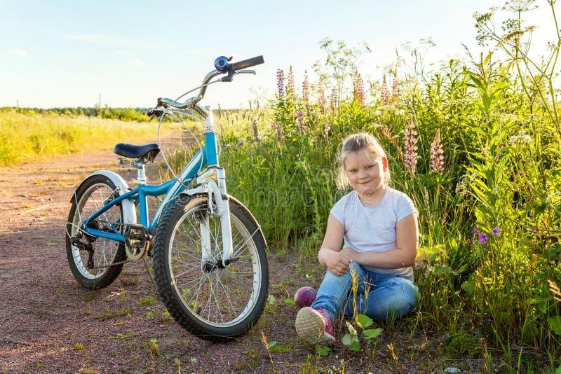 Uśmiechnięta mała dziewczynka blisko bicyklu fotografia stock